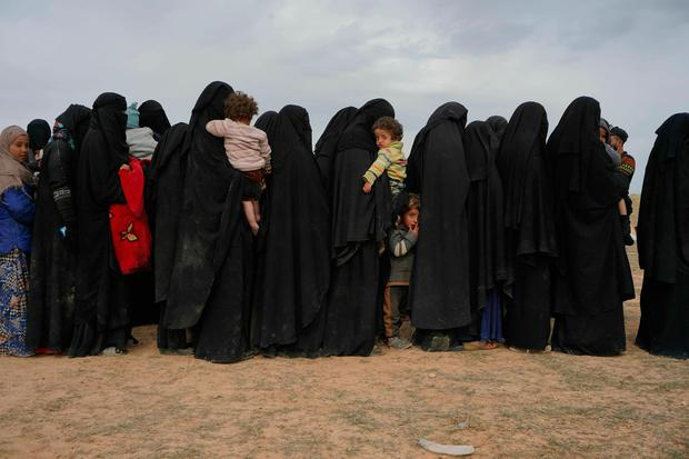 Women and children who were evacuated out of the last territory held by Islamic State militants wait to be screened outside Baghouz, Syria, Tuesday, March 5, 2019. (AP Photo/Andrea Rosa)