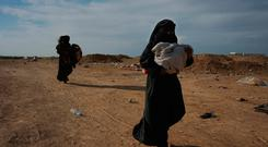 Women who were evacuated out of the last territory held by Islamic State militants carry their children outside Baghouz, Syria, Tuesday, March 5, 2019. AP Photo/Andrea Rosa)