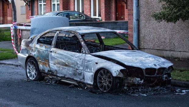 A burnt-out car on Saddlers Drive a short distance from the incident