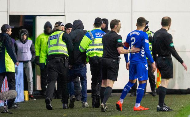 Rangers James Tavernier is pulled away from a fan that ran onto the pitch at half time during the Ladbrokes Scottish Premiership match at Easter Road, Edinburgh. Jeff Holmes/PA Wire