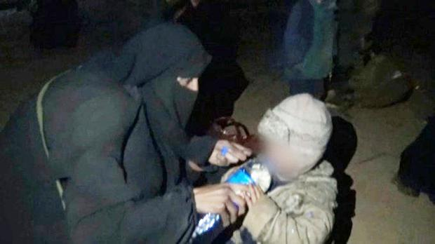 Videograb captured by an ITV cameraman of a woman believed to be Lisa Smith giving water to a young child in a camp in Syria