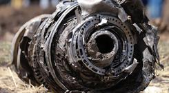 Mystery: Part of a mangled jet engine lies on the ground at the crash site. Photo: REUTERS