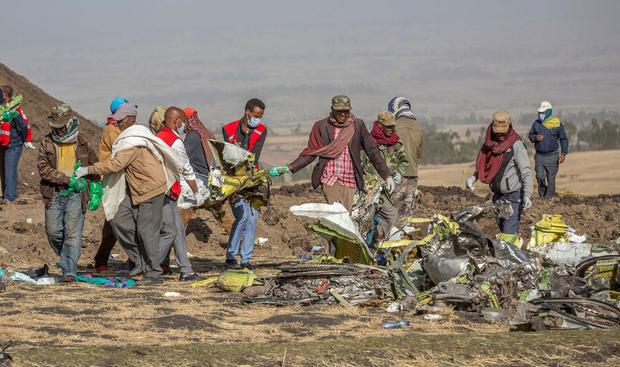 Workers comb the wreckage of the Ethiopian Airlines flight near Bishoftu, south of Addis Ababa, yesterday. AP Photo/Mulugeta Ayene