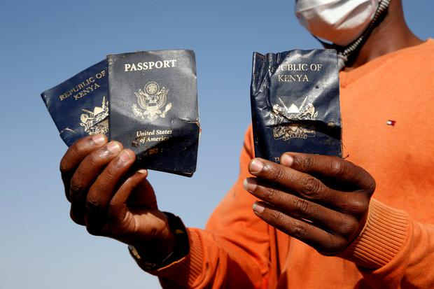 A man holds passengers' passports found at the scene of the Ethiopian Airlines Flight ET 302 plane crash, near the town of Bishoftu, near Addis Ababa