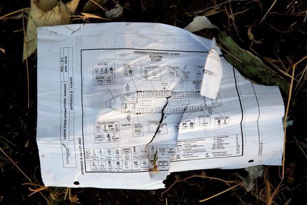 A page of a flight crew operations manual is seen at the scene of the Ethiopian Airlines Flight ET 302 plane crash