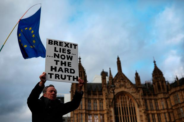 Opposition: An anti-Brexit protester in the rain ahead of the meaningful vote in parliament yesterday which saw the UK prime minister's deal defeated. Photo: Dan Kitwood/Getty Images