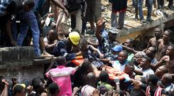 Emergency: Hundreds of people surround the collapsed building as children are pulled from the wreckage by rescue workers. Photo: Reuters/Temilade Adelaja