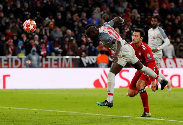 ON THE HEAD: Sadio Mane grabs Liverpool's third goal at the Allianz Arena. Pic: Reuters/Andrew Boyers