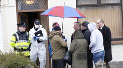 'Sad day': Neighbours gather as gardaí probe the scene in Convoy, east Donegal yesterday. Picture: North West Newspix