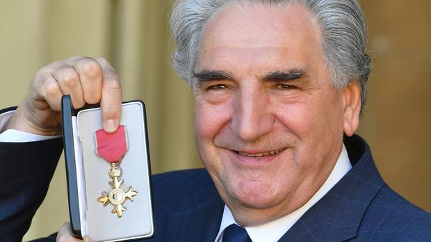 Jim Carter holds his OBE following an investiture ceremony at Buckingham Palace (John Stillwell/PA)