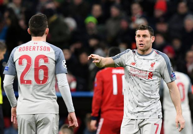Liverpool midfielder James Milner, right, gives instructions to his teammate Andy Robertson during their Champions League clash with Bayern Munich. AP Photo/Kerstin Joensson