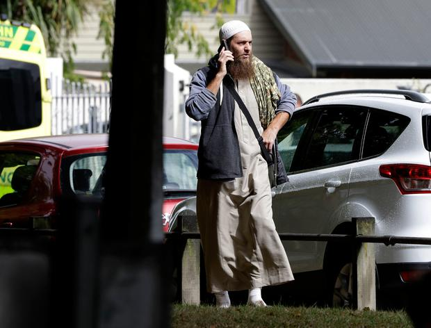 A man talks on his mobile phone across the road from a mosque in central Christchurch, New Zealand. (AP Photo/Mark Baker)