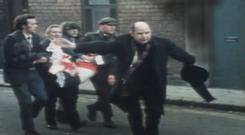 Fr Edward Daly waves a white handkerchief as he tries to escort 17-year-old Jackie Duddy away after being shot on Bloody Sunday. Duddy died of his injuries soon after and Daly administered the last rites