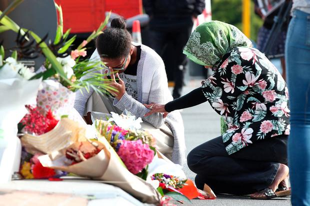 Tearful tribute: Locals lay flowers in tribute to those killed and injured at the Al Noor Mosque. Photo: Getty