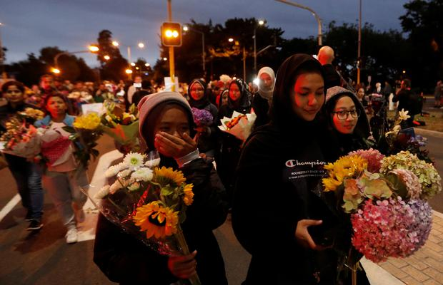 People reacts as they move the flowers after police removed a police line, outside Masjid Al Noor in Christchurch, New Zealand, March 16, 2019. REUTERS/Jorge Silva