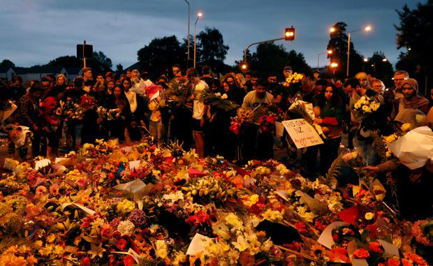 People prepare to move the flowers after police removed a police line, outside Masjid Al Noor in Christchurch, New Zealand, March 16, 2019. REUTERS/Jorge Silva