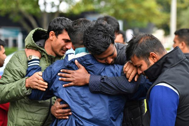 Friends of a missing man grieve outside a refuge center in Christchurch, Sunday, March 17, 2019. The live-streamed attack by an immigrant-hating white nationalist killed dozens of people as they gathered for weekly prayers in Christchurch. (Mick Tsikas/AAP Image via AP)