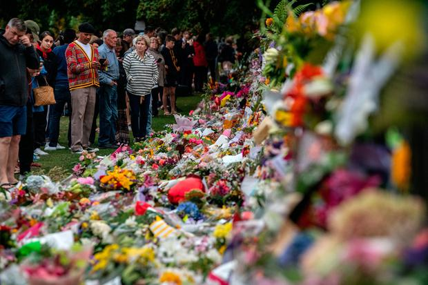 People pause next to flowers and tributes by the wall of the Botanic Gardens on March 17, 2019 in Christchurch, New Zealand. Photo by Carl Court/Getty Images