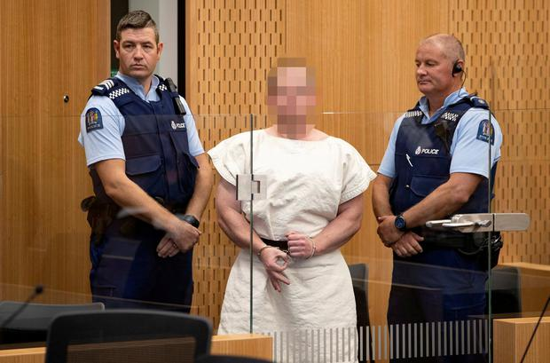 Brenton Tarrant (face obscured) making the 'white power' symbol in Christchurch court. Photo: Mark Mitchell/New Zealand Herald/Pool via Reuters