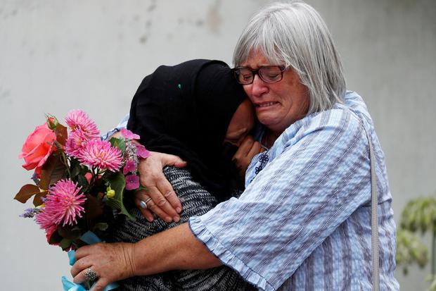 Tears: Women embrace near Al Noor mosque in Christchurch, New Zealand. Photo: Reuters/Jorge Silva