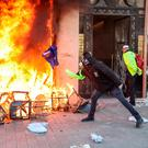 Anger: A yellow vest protester throws an EU flag into a burning shop on the Champs-Élysees in Paris at the weekend. Photo: Getty Images