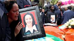 A woman mourns next to coffins during the funeral of crash victims in Addis Ababa. Photo: Reuters/Tiksa Negeri