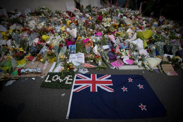 Mourners lay flowers on a wall outside the Al Noor mosque in Christchurch, New Zealand, Monday, March 18, 2019