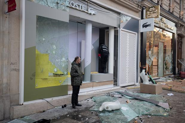 A man stand in front of a damaged shop on the Champs Elysees avenue during a demonstration by the