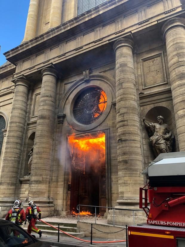 Members of the fire brigade run as a Saint-Sulpice church is seen on fire in Paris, France, March 17, 2019