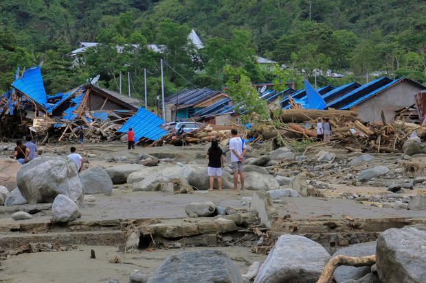 People stand as they look at damaged houses after a flash flood in Sentani, Papua, Indonesia, March 17, 2019 in this photo taken by Antara Foto. Antara Foto/Gusti Tanati/ via REUTERS