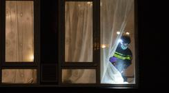 A forensic expert looks for clues in a house where the suspect of a shooting incident was arrested in Utrecht, Netherlands, Monday, March 18, 2019. A gunman killed three people and wounded nine others on a tram in the central Dutch city of Utrecht. (AP Photo/Peter Dejong)