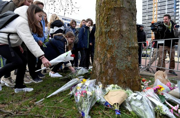 Children place flowers at the site of a shooting in Utrecht, the Netherlands March 19, 2019. REUTERS/Piroschka van de Wouw