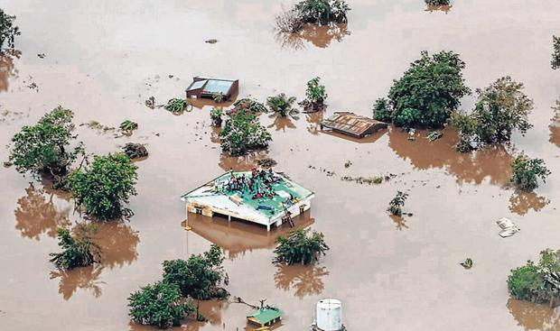 Stranded: People on a roof surrounded by flooding in an area affected by Cyclone Idai in Beira, Mozambique. Photo: Rick Emenaket / AFP