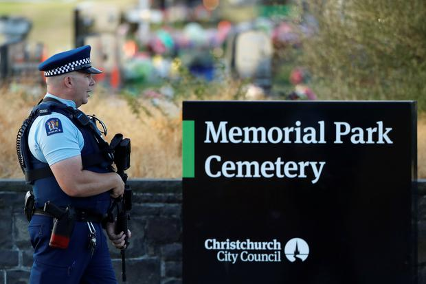 An armed policeman stands guard as the burial ceremony of the victims of the mosque attacks takes place at the Memorial Park Cemetery in Christchurch, New Zealand March 20, 2019. REUTERS/Jorge Silva