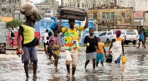In this photo taken on Friday, March 15, 2019 and provided by the International Red Cross, people carry their personal effects after Tropical Cyclone Idai, in Beira, Mozambique. (Denis Onyodi/IFRC via AP)