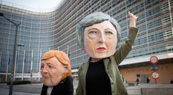 Glum: Anti-Brexit protesters dressed as Theresa May and Angela Merkel in Brussels. Picture: PA