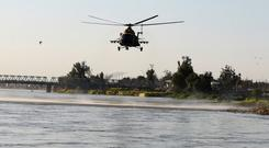 An Iraqi rescue helicopter searches for survivors over the site where an overloaded ferry sank in the Tigris river near Mosul in Iraq. Photo: Reuters