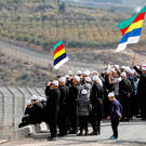 On the border: Members of the Druze community on the Israeli-controlled sector of the Golan Heights use loud-hailers to talk to fellow Druze in Syria. Photo: Getty Images