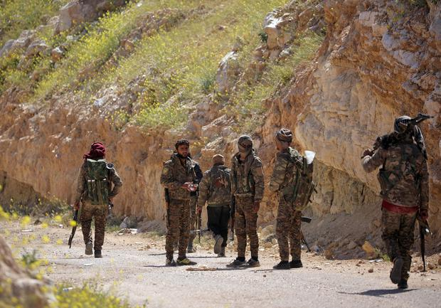 FILE PHOTO: Fighters from the Syrian Democratic Forces (SDF) stand together in the village of Baghouz, Deir Al Zor province