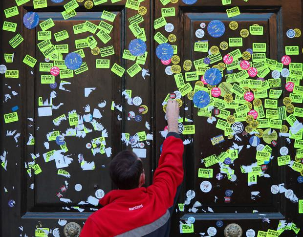 Workers peeling off stickers left on the Cabinet Office door in Whitehall, London, left by anti-Brexit campaigners after they took part in the People's Vote March. Photo: PA