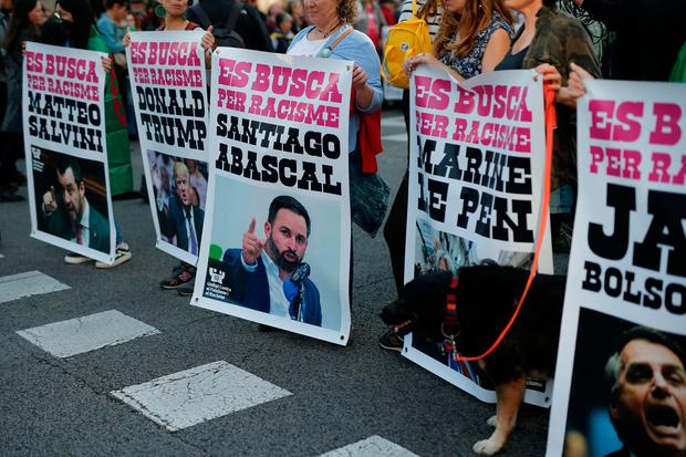 Protest: People hold 'Wanted for racism' posters with pictures of politicians including Italy's Matteo Salvini (far left) in Barcelona. Photo: Getty