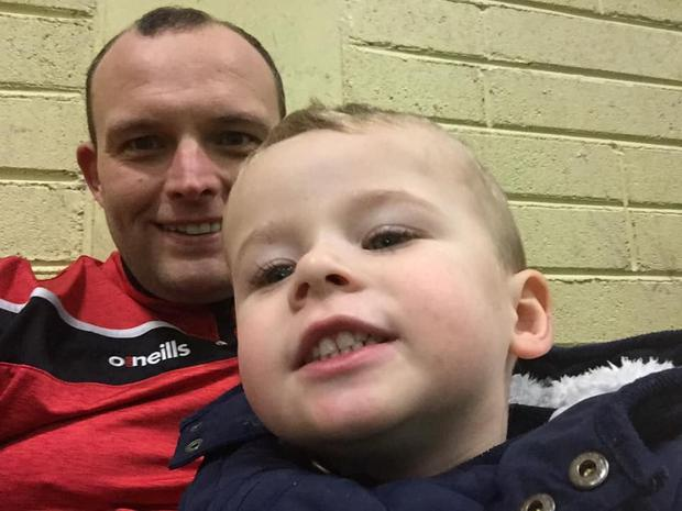 Paul Higgins pictured with his toddler son who remains in a serious but stable condition in hospital