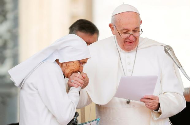Worship: A nun who had been working on the missions in Africa kisses Pope Francis's hand during an audience in St Peter's Square at the Vatican yesterday. Photo: Reuters /Remo Casilli