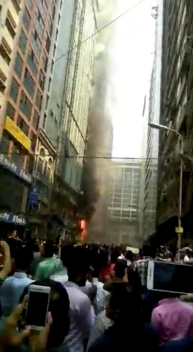 People stand outside a building on fire, in Dhaka, Bangladesh March 29, 2019 in this picture grab obtained from a social media video. MAX SECURE LIMITED/via REUTERS