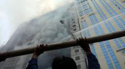 A person looks on as firefighters attempt to extinguish a fire at a multi-storey commercial building in Dhaka, Bangladesh, March 28, 2019. REUTERS/Mohammad Ponir Hossain