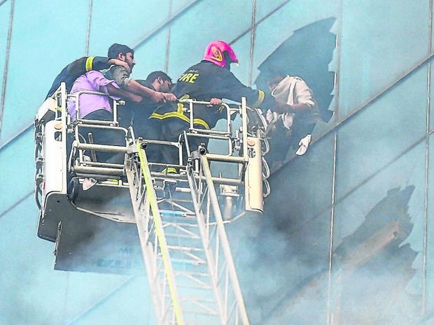 Firefighters rescue a worker from the burning office building. Photo: MUNIR UZ ZAMAN/AFP/Getty Images