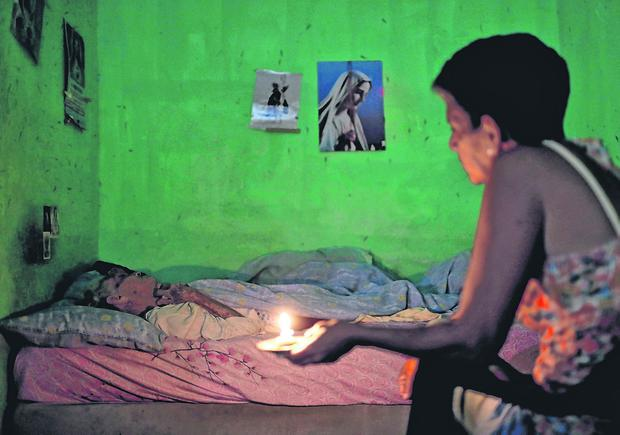 Home care: Ninoska Blanco sits with her sick mother Alexandrian Blanco in Caracas during one of the many power blackouts that have hit Venezuela. Photo: AP Photo/Natacha Pisarenko