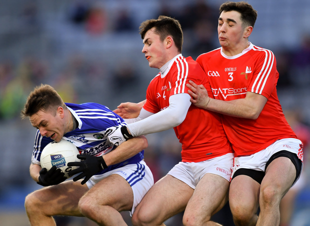 Laois' Ross Munnelly is tackled by Louth's Dan Corcoran (c) and Emmet Carolan during their NFL Division 3 match in February
