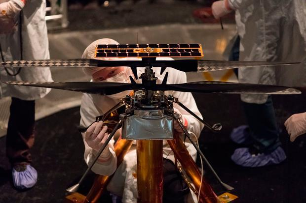 Members of the NASA Mars Helicopter team attaching a thermal film to the exterior of the flight model of the Mars Helicopter at NASA's Jet Propulsion Laboratory in Pasadena, California. Photo: NASA/PA
