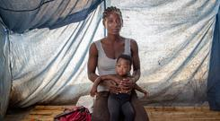 HAPPY MOTHER'S DAY: Mother-of-three Emily Zebia with her youngest child, nine-month-old Pilirani, and all her belongings — a small bundle of clothes and a Bible. Until the cuurent floods subside, she will share this tent at Nyachikadza Displacement Camp, Malawi, with 19 other women and children. And then her troubles will really begin. Picture: Gavin Douglas